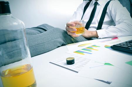 jovenes tomando alcohol: un joven hombre de negocios sentado en su escritorio de oficina con un vaso con una bebida alcoh�lica en la mano Foto de archivo