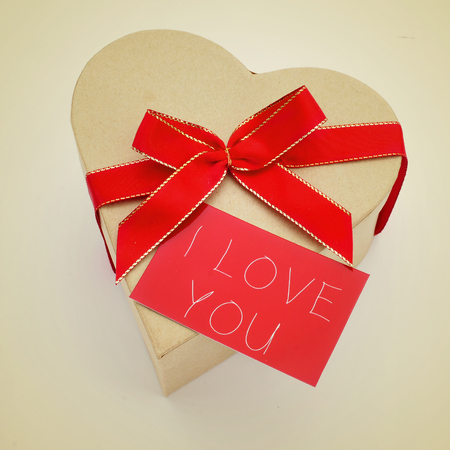 a heart-shaped gift box with a red ribbon bow and a red signboard with the text I love you written in it, with a retro effect photo