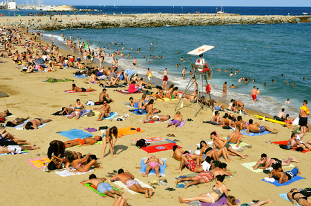 bathers: Barcelona, Spain - August 19, 2014: A crowd of bathers in La Barceloneta Beach in Barcelona, Spain. This popular beach hosts about 500,000 visitors from everywhere during the summer season Editorial