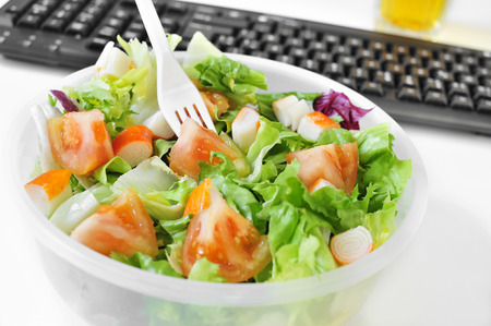lunch: closeup of a salad in a plastic container on the desk of an office Stock Photo