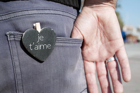 i t: a heart-shaped chalkboard with the text je t aime, I love you written in french, in the back pocket of the trousers of a young man