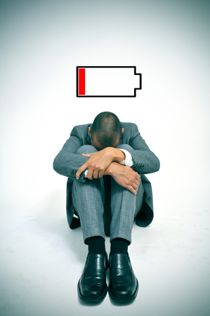 curled up: a young businessman curled up in the floor with his head between his knees and an illustration of a low battery Stock Photo