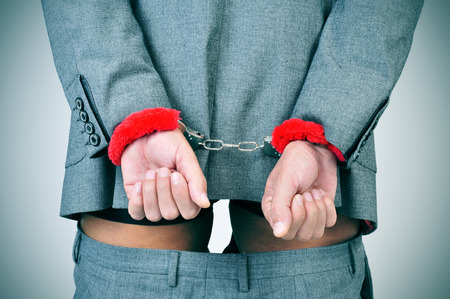 a man in suit with his wrists locked in the back with sexy fluffy handcuffs and his pants down