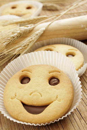 breakfast smiley face: closeup of some smiley biscuits on a wooden worktop with some ears of wheat and a wooden rolling pin