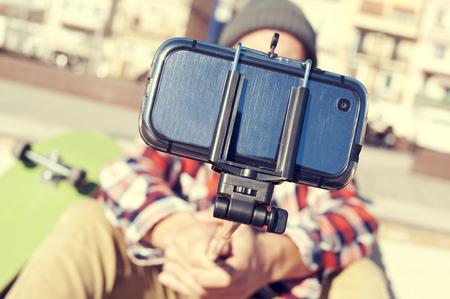 un patineur prendre un auto-portrait avec un bâton de Selfie