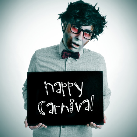 disguised: a man dressing a zombie costume with a black signboard with the text happy carnival written in it