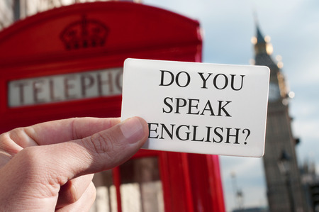 great britain: a man holding a signboard with the text do you speak english? with a red telephone booth and the Big Ben in the background, in London, UK Stock Photo
