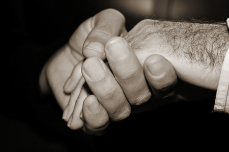 geriatrician: closeup of a young man holding the hand of an old man, in black and white