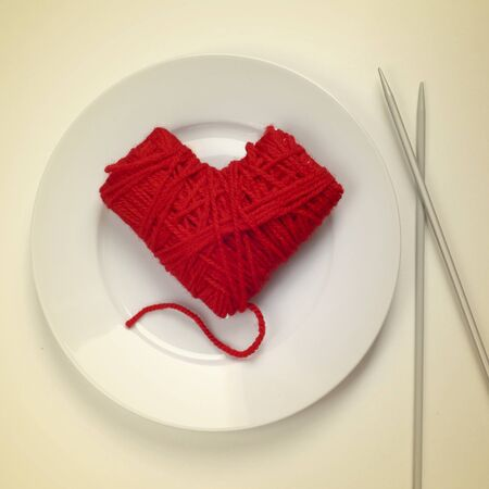 knitting needles: a heart-shaped ball of yarn in a plate and knitting needles at the side, as the flatware, with a retro effect Stock Photo