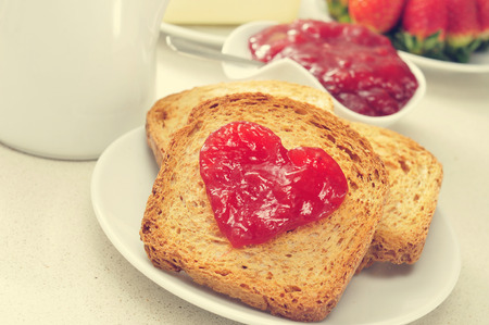 marmalade: jam forming a heart on a toast, on a set table for breakfast Stock Photo