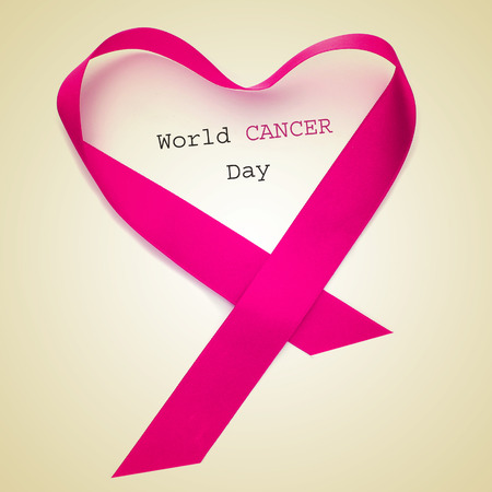 cancer research: the text world cancer day and a pink ribbon forming a heart on a beige background Stock Photo