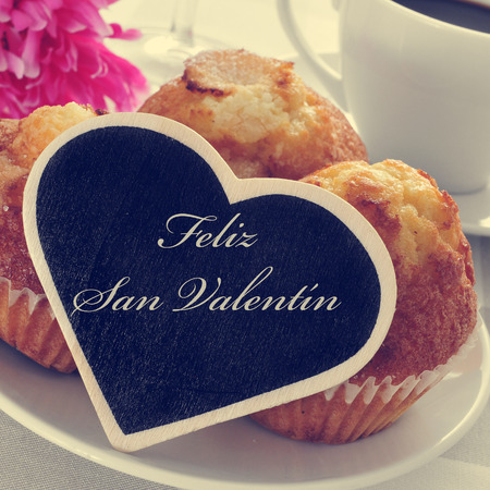 valentin: the text feliz san valentin, happy valentines day in spanish, written in a heart-shaped signboard, in a plate with magdalenas, spanish plain muffins
