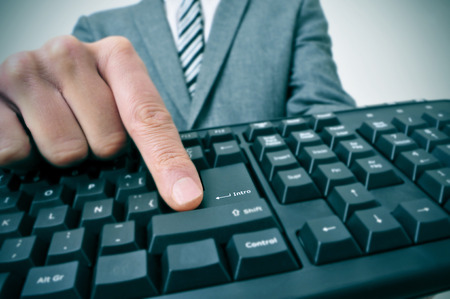 inter: closeup of a businessman pressing the inter key of a computer keyboard