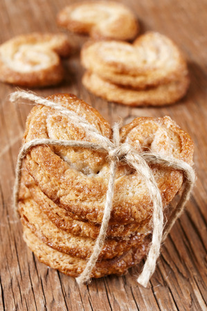 puff pastry: some palmeras, spanish palmier pastries, tied with a string on a rustic wooden table Stock Photo