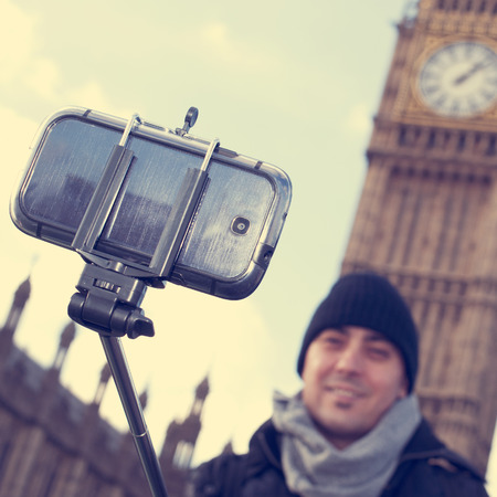 to stick: man taking a self-portrait with a selfie stick in front of the Big Ben in London, United Kingdom, with a filter effect