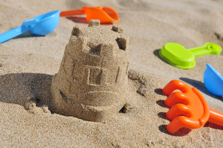 sandcastle: closeup of a sandcastle and some toy shovels on the sand of a beach Stock Photo