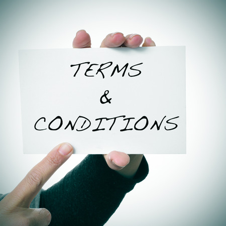 law office: closeup of the hand of a young woman showing a signboard with the text terms and conditions written in it Stock Photo