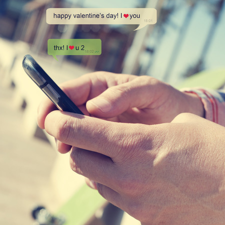 a young man sending a text message with a smartphone with the text Happy valentines day, I love you Banco de Imagens
