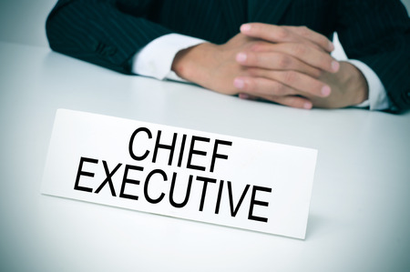 chief executive officers: a man in suit sitting at a desk with a signboard in front of him with the text chief executive written in it Stock Photo