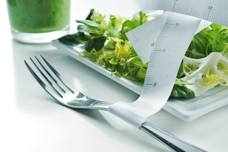 escarole: closeup of a plate with a green salad and a measuring tape and a green smoothie, depicting the concept of dieting or to stay fit