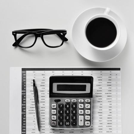 haute angle de tir d'un bureau avec une calculatrice, un stylo, un bilan, des lunettes et une tasse de café dans un bureau