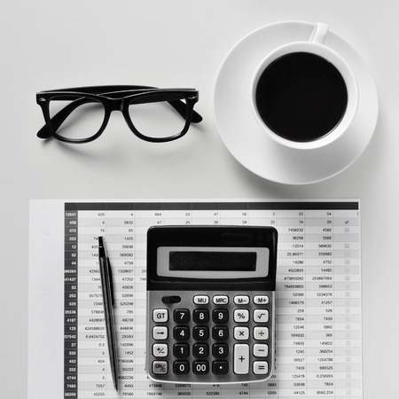 high-angle shot of a desk with a calculator, a pen, a balance sheet, eyeglasses and a cup of coffee in an office Stock Photo