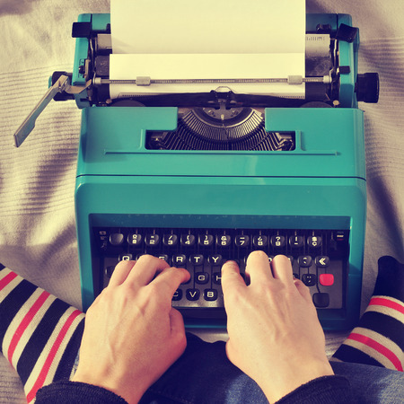 prose: a young man typing in an old typewriter on the bed, with a retro effect