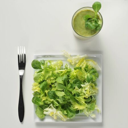escarole: high-angle shot of a plate with a green and a green smoothie on a white table