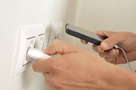 plugging: closeup of the hands of a man plugging in the plug of his smpartphone in a socket
