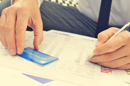 outgoings: closeup of a young man checking the information of his credit card in a bill