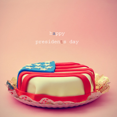 president's day: the text Happy Presidents Day and a cake ornamented with the flag of the United States on a pink background Stock Photo