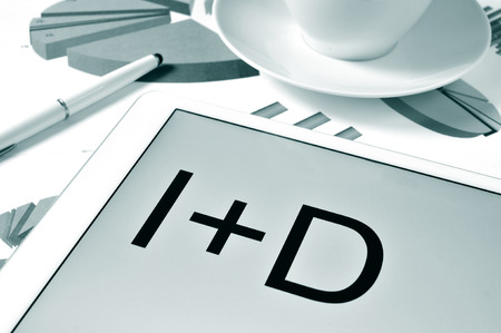 d i y: the text I plus D, investigacion y desarrollo, research and development in spanish in the screen of a tablet, on a desk with charts, in black and white Stock Photo