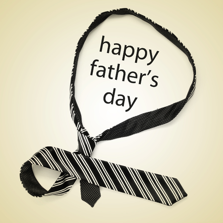 paternity: a necktie and the sentence happy fathers day on a beige background, with a retro effect Stock Photo