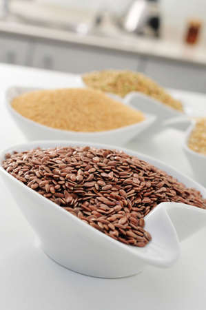 linum usitatissimum: closeup of a bowl with brown flax seeds, and other seeds and cereal in the background, on the countertop of a kitchen