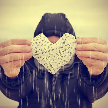 telegrama: un joven bajo la lluvia mostrando un corazón hecho-up con tiras de papel con el texto del día de san valentín feliz, con un efecto de filtro Foto de archivo