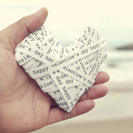 telegrama: la mano de un hombre joven sosteniendo un corazón hecho-up con tiras de papel con el texto del día de san valentín feliz, con un efecto de filtro