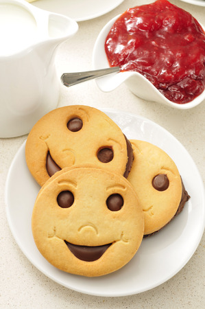 breakfast smiley face: a plate with some smiley biscuits, a pot with milk and a bowl with jam on a set table