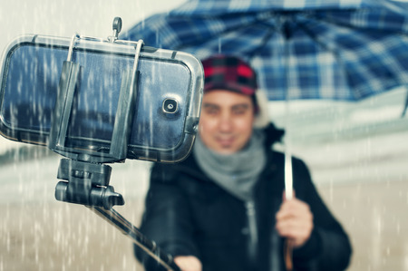 a young man taking a self-portrait with a selfie-stick under the rain Stock Photo