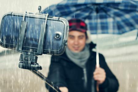 un jeune homme de prendre un auto-portrait avec un Selfie-bâton sous la pluie Banque d'images