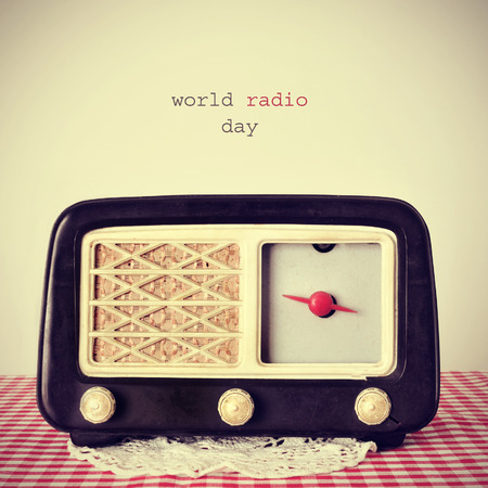 receptor: the text world radio day and an antique radio receptor on a table covered with a red and white checkered tablecloth, with a retro effect