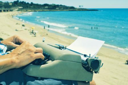 Un jeune homme frappe dans une vieille machine à écrire sur la plage Banque d'images - 36392756