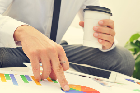 budget crisis: closeup of a young businessman with a cup of coffee in his hand checks some charts