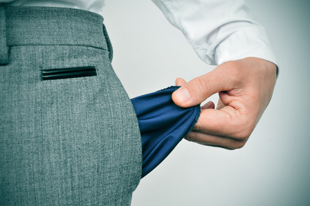 hand in pocket: a broke businessman showing his empty pocket Stock Photo