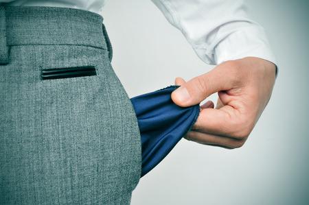 bolsa dinero: un hombre de negocios en quiebra mostrando su bolsillo vacío Foto de archivo