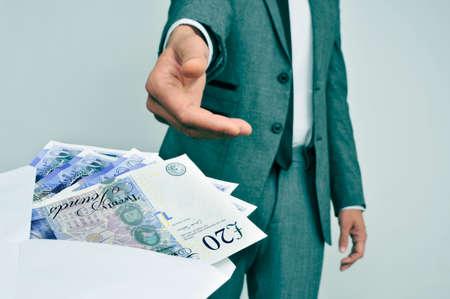 un homme en costume en prenant une enveloppe pleine de billets en livres sterling