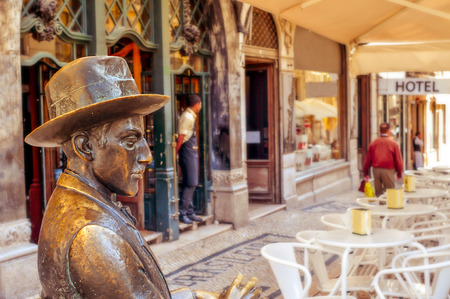 chiado: Lisbon, Portugal - March 18, 2014: Statue of Fernando Pessoa outside of Cafe A Brasileira in Lisbon, Portugal. This iconic statue and the cafe itself are visited by thousands of tourists