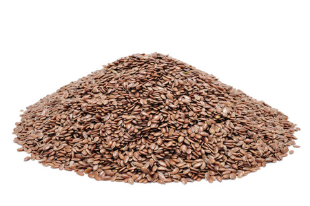 linum usitatissimum: a pile of brown flax seeds on a white background