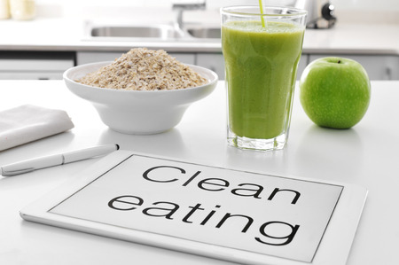 eating fruit: a tablet with the text clean eating written in it and a bowl with oatmeal cereal, a glass with a green smoothie and an apple on the kitchen table