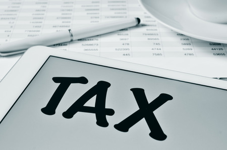 outgoings: the word tax written in the screen of a tablet, on a table with a balance sheet