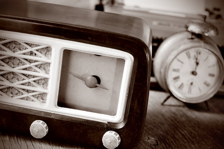 sepia toning: an antique radio receptor and some other antiques, such an alarm clock and a typewriter in the background, in sepia toning